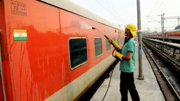Indian Railways - A railway worker sanitises a coach of Rajdhani Express